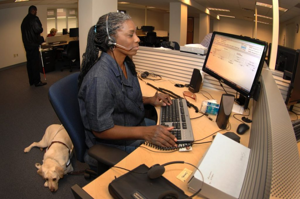 Beverly Redic employs Job Access with Speech, an interactive screen reader with text-to-speech capabilities to help a customer at the Telephone Consolidated Operation Center at Travis. (U.S. Air Force photo/Nan Wylie)