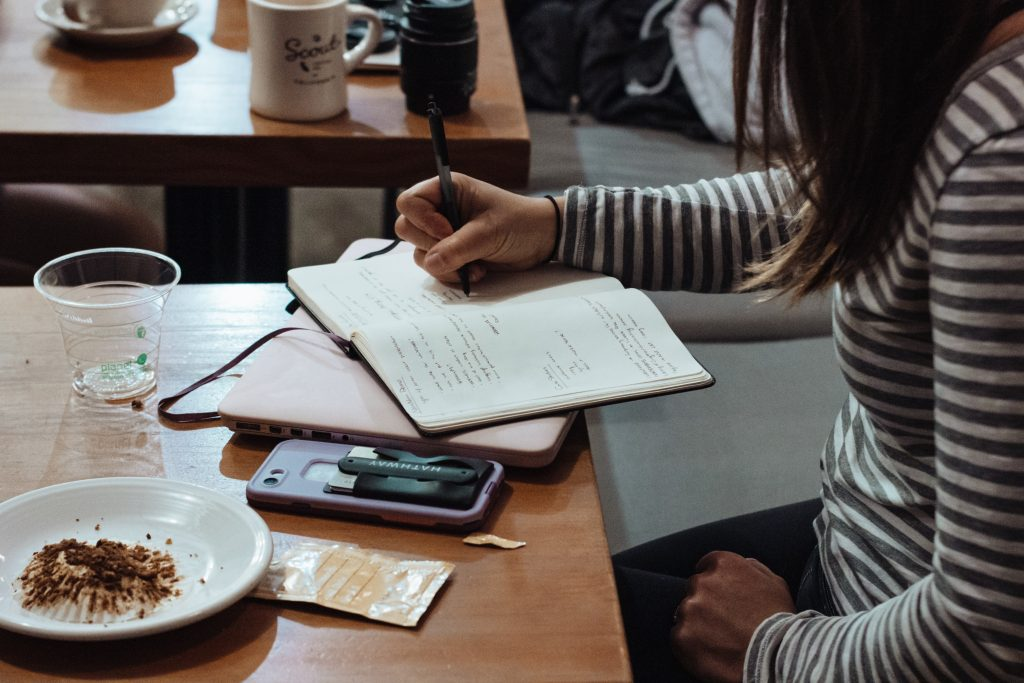 Female writing notes in a coffee shop with her phone face down on the table.